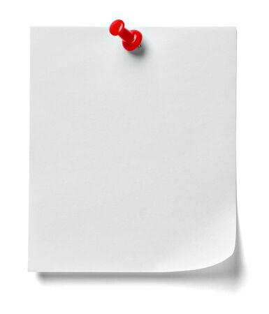 Close up di una nota carta con una puntina rossa su sfondo bianco