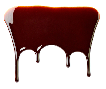 close up of chocolate syrup leaking on white background