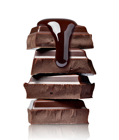 close up of chocolate pieces stack and chocolate syrup on white background