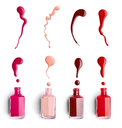close up of  a nail polish bottle and drop on white background