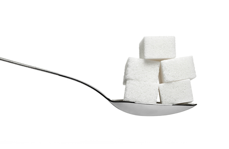 close up of  sugar cubes and a spoon on white background