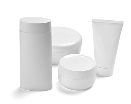 Cerca de un recipiente y tubo de crema de belleza blanca sobre fondo blanco. Foto de archivo