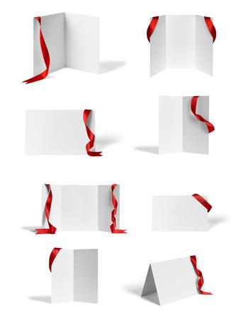 raccolta di vari volantini piegati in bianco o un calendario desktop con nastro su sfondo bianco. ognuno è girato separatamente Archivio Fotografico