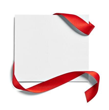 Cerca de una tarjeta de nota con lazo de cinta roja sobre fondo blanco. Foto de archivo