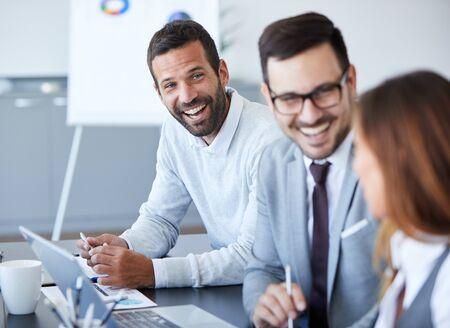 Ein Porträt eines jungen lächelnden Geschäftsmannes ein Treffen und eine Präsentation im Büro. Unternehmenskonzept