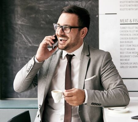 portrait of a young businessman drinking coffe and talking on cell phone i na restaurant coffee bar Imagens