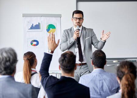 Junger Geschäftsmann mit einer Rede von einem Whiteboard während eines Konferenzgeschäftstreffens in einem Büro. Geschäftskonzept