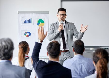 Young busnessman having a speech by a whiteboard during a conference business meeting in an office. Business concept
