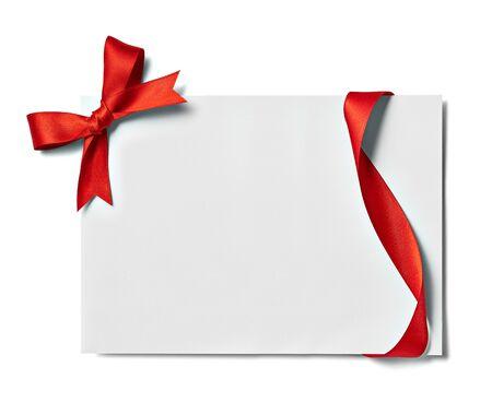 Cerca de una tarjeta de nota con lazo de cinta roja sobre fondo blanco.