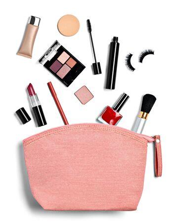 Cerca de un neceser lleno de maquillaje sobre fondo blanco. Foto de archivo