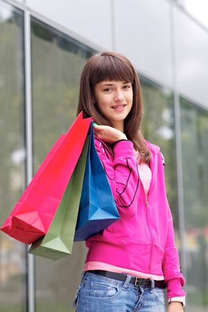 beautiful teenage girls talking on cell phone and holding shopping bags