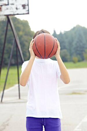 teenage girl holding basket ball in school court