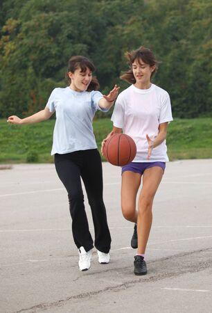 teenage girls playing basketball game in school court
