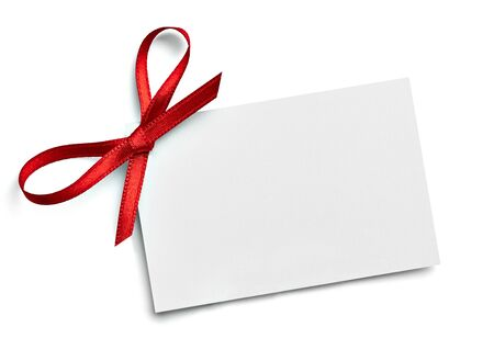 close up of a note card with red ribbon bow on white background Zdjęcie Seryjne