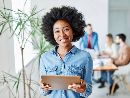 portrait of a smiling young businesswoman holding a tablet in the office Reklamní fotografie