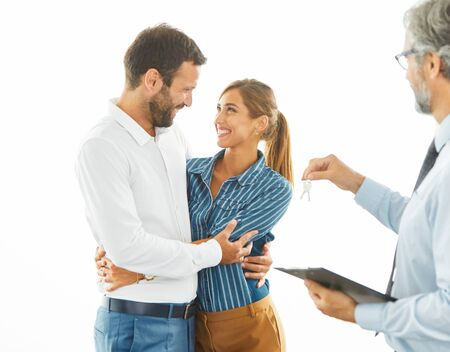 Happy young couple buying a new house receiving the keys