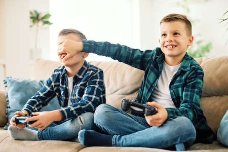 School age brothers laughing and having fun together at home playing games with console