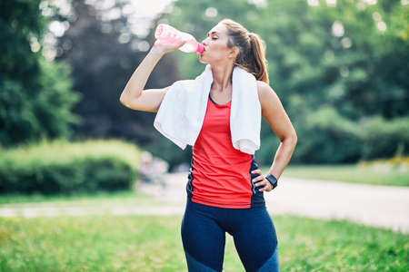 Portrait of a young fitness woman drinking water after exercising in a park outdoors
