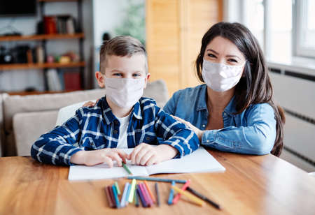 mother teaching son and helping him with homework at home, both of them wearing protective masks Banque d'images