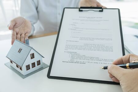 Real estate agent and customer signing contract to buy house, insurance or loan real estate. Stock Photo