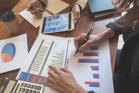 Equipo de negocios intercambiando ideas y discutiendo con datos financieros y gráfico de informes. Concepto de trabajo de reunión de trabajo en equipo.