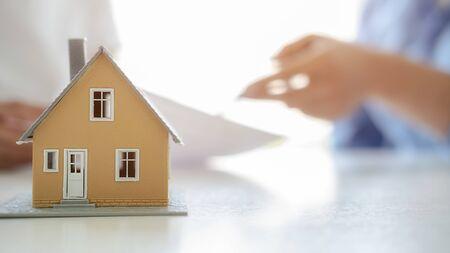Modelo de casa con agente y cliente discutiendo sobre contrato para comprar, obtener seguro o préstamo de bienes raíces o antecedentes de propiedad.
