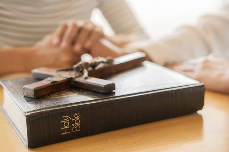 Christian woman praying with hands together on holy bible and wooden cross. Woman pray for god blessing to wishing have a better life and believe in goodness. Stock Photo