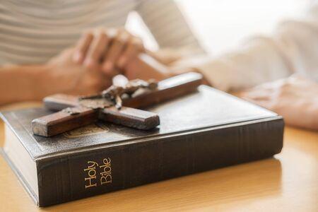 Christliche Frau, die mit den Händen zusammen auf heiliger Bibel und Holzkreuz betet. Frauen beten um Gottes Segen, um ein besseres Leben zu wünschen und an das Gute zu glauben. Standard-Bild