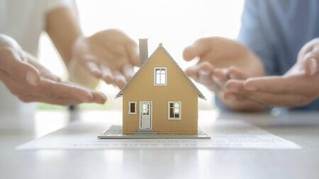 House model with agent asking costumer for contract to buy, get insurance or loan real estate or property.