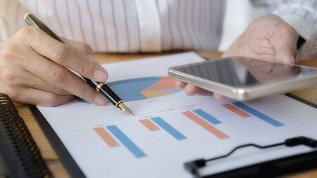 Kobiety biznesu przy użyciu smartfona do sprawdzania wykresu wydajności firmy w biurze. Pomysł na biznes. Zdjęcie Seryjne