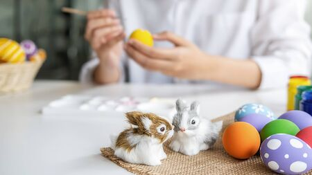 Easter eggs and Decoration on white desk with happy woman painting eggs background. Family preparing for Easter.