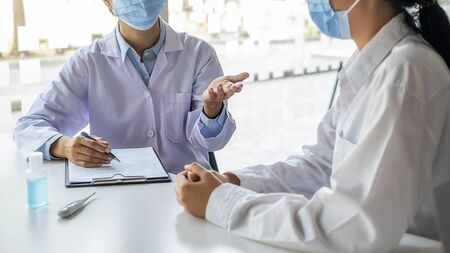 Doctor consulting patient, working on diagnostic examination on Coronavirus disease while writing on prescription record information document in clinic or hospital office. Medical and Health concept.