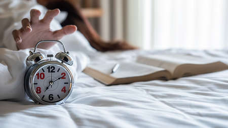 Asian lazy woman want to putting her alarm clock off in the morning with soft morning light. Morning lifestyle concept.