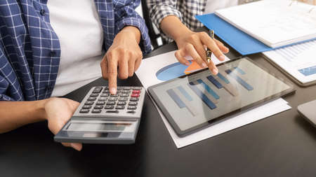 Business woman using calculator to calculate business data, accountancy document at home office. Banque d'images