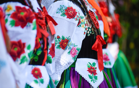 Regional, folklore costumes, colorful handmade shirts with stripes and symbols embroidered. During Corpus Christi parade.