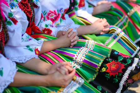 Regional, folklore costumes, colorful handmade shirts and skirts with stripes and symbols embroidered. During Corpus Christi parade.