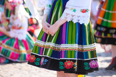 Regional, folklore costumes, colorful handmade skirts with stripes and symbols embroidered. During Corpus Christi parade. Stock Photo