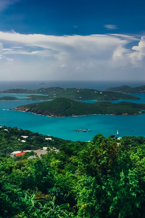 Aerial, vertical view on the turquoise sea and green hills around.