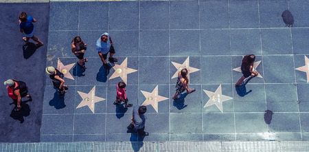 Hollywood/Los Angeles/California/USA - 07.19.2013: View from the top at lots of people walking on the sidewalk Walk Of Fame with the stars of famous people, on the sunny day.