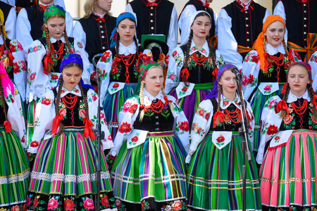 Lowicz / Poland - May 31.2018: Local, regional choir of young women and men dressed in folklore costumes. Colorful skirts and pants, white shirts, vivid head kerchief, black vests. Stock fotó - 115825446