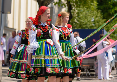 Lowicz / Poland - May 31.2018: Corpus Christi church holiday procession. Local women dressed in folk, regional costumes with colorful stripes, embroidered folklore symbols, white shirts. Sunny day.