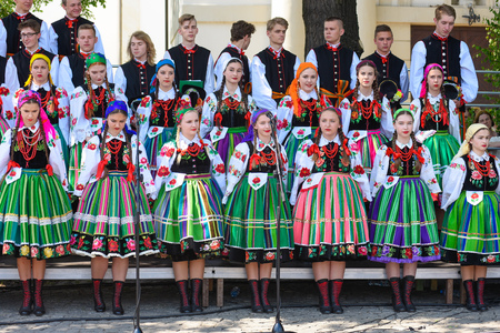 Lowicz  Poland - May 31.2018: Local, regional choir of young women and men dressed in folklore costumes. Colorful skirts and pants, white shirts, vivid head kerchief, black vests.
