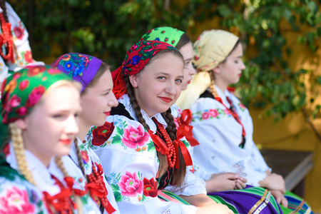 Lowicz / Poland - May 31.2018: Local, regional choir of young women and men dressed in folklore costumes. Colorful skirts and pants, white shirts, vivid head kerchief, black vests. Stock fotó - 115825500