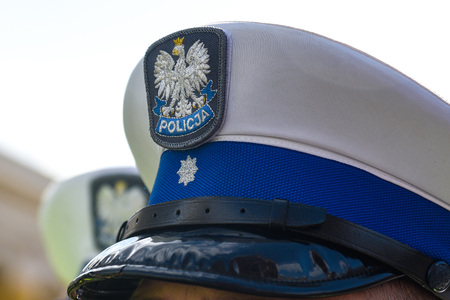 Police hat with polish emblem of white eagle and police sign.