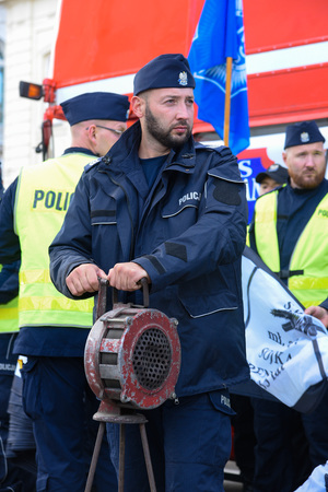Warsaw / Poland - October.02.2018: Demonstration, national protest of police officers for fair work wages. Policeman holding siren device. Editorial