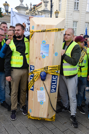 Warsaw / Poland - October.02.2018: Demonstration, national protest of police officers for fair work wages. Group of policeman holding coffin with police sign and blue police neon.