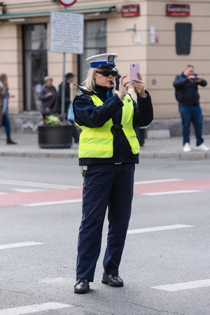 Warsaw / Poland - October.02.2018: Police woman standing on the cross road and controlling the traffic. Dressed in a police uniform with yellow west. Editorial