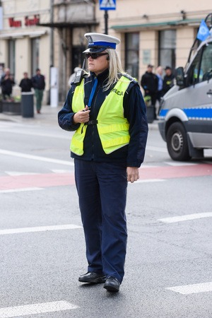Warsaw / Poland - October.02.2018: Police woman standing on the cross road and controlling the traffic. Dressed in a police uniform with yellow west.