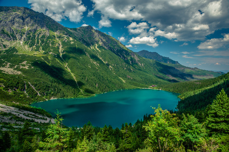 View on the turquoise color lake between high and rocky mountains. Beautiful alpine landscape. Фото со стока