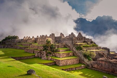 Mystical view on the Machu Picchu city ruins covered with fog with sun rays passing trough the clouds. Sacred city of Inca during the sunrise.